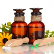 Medicine bottles with tablets and flowers isolated on white — Stock Photo