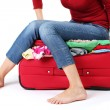 The girl is trying to close suitcase crammed on white background — Stock Photo #13352298