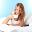 Young beautiful woman on bed with cup of coffee on blue background — Stock Photo #13352518