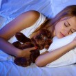 Young beautiful woman with toy bear sleeping on bed in bedroom — 图库照片 #13352526