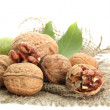 Walnuts with green leaves on burlap, isolated on white - Stock Photo