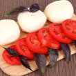 Tasty mozzarella with tomatoes on chopping board on mat - Photo