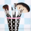 Makeup brushes in a black polka-dot cup on colorful background - Stock Photo