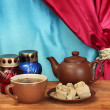 图库照片: Teapot with cup and saucer with sweet halva on wooden table on a backgroun