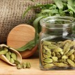 Jar of green cardamom with rocket on canvas background close-up — Stock Photo #13359537