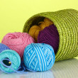 Colorful yarn for knitting in green basket on green background — Stock Photo #13359737