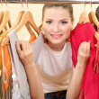 Stock Photo: Beautiful young woman near rack with hangers