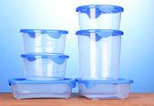 Kunststoffbehälter für lebensmittel auf holztisch auf blauem hintergrund — Stockfoto