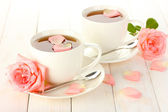 Cups of tea with roses on white wooden table — Stock Photo
