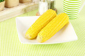 Boiled corn and flowers on a white background — Stock Photo