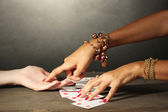 Reading the lines hand and woman's hands on grey backcground — Stock Photo