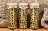 Glass jar with tinned capers on sack background close-up — Stock Photo