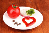 Ripe tomato and spices on plate on wooden table — Stock Photo