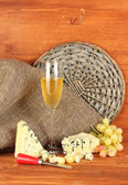 Composition of blue cheese and a glass of wine with grapes on wooden backgr — Stock Photo
