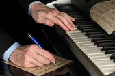 Man hands playing piano and writes on parer for notes — Stock Photo