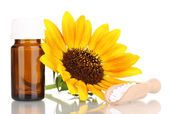 Medicine bottle with tablets and flower isolated on white — Stock Photo