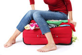The girl is trying to close suitcase crammed on white background — Stockfoto