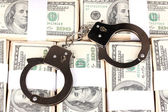 Handcuffs on the packs of dollars close-up — Stock Photo