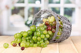 Ripe green grapes in basket on wooden table on window background — Stock Photo