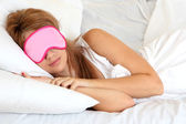 Young beautiful woman sleeping in bed with eye mask — Stock Photo