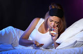 Young beautiful woman with pills lying on bed in bedroom — Stock Photo