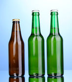 Bottles of beer on blue background — Stock Photo