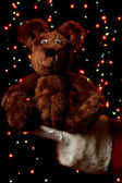 Santa Claus hand holding toy bear on bright background — Stock Photo