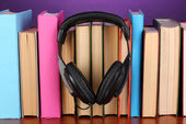 Headphones on books on wooden table on purple background — 图库照片