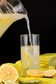 Citrus lemonade in glass and pitcher of citrus around on yellow fabric on wooden table close-up — Stock Photo