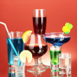 Variety of alcoholic drinks on red background — Stock Photo #13369184