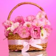 Bouquet of eustoma flowers in basket, on pink background — Stock Photo
