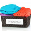 Donation box with clothing isolated on white - Stock Photo