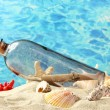 Royalty-Free Stock Photo: Glass bottle with note inside on sand, on blue sea background