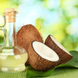 Decanter with coconut oil and coconuts on green background — Stock Photo #13369709