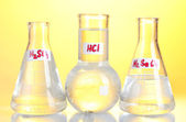 Test-tubes with various acids and chemicals on yellow background — Stock Photo