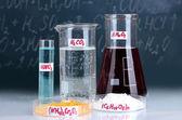 Tubos de ensayo con diversos ácidos y otros productos químicos en el fondo de la pizarra — Foto de Stock