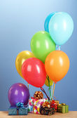 Colorful balloons holding a gifts on a wooden table on blue background — ストック写真