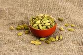 Groene cardamon in ceramical kom op doek achtergrond close-up — Stockfoto