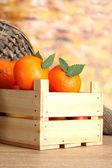 Turuncu zemin üzerine masada ahşap kutusunda yaprakları ile olgun lezzetli mandalina — Stok fotoğraf