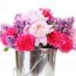 Royalty-Free Stock Photo: Beautiful spring flowers in metal bucket isolated on white