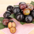 Rip plums on basket on wooden table - Stock Photo