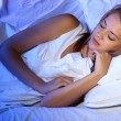Young beautiful woman sleeping on bed in bedroom — Stock Photo #13395611