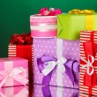 Colorful gifts on green background — Stock Photo