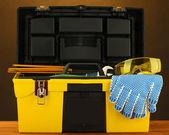 öppna gul verktygslåda med verktyg på brun bakgrund närbild — Stockfoto