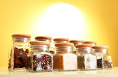 Powder spices in glass jars on yellow background — Stock Photo