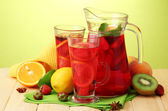 Sangria in jar and glasses with fruits, on wooden table, on green background — Stock Photo