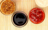 Various sauces on bamboo mat — Stock Photo