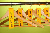 Wooden clothes hangers as sale symbol on green background — Stock Photo