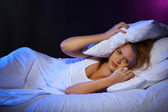 Young beautiful woman lying on bed in bedroom — Stock Photo