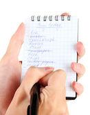 женщины рука держа ноутбук с крупным планом список покупок — Стоковое фото